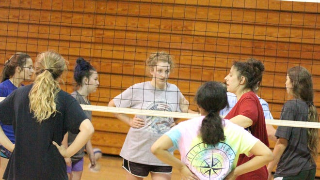 Jordan Devine works with underclassmen during volleyball practice.