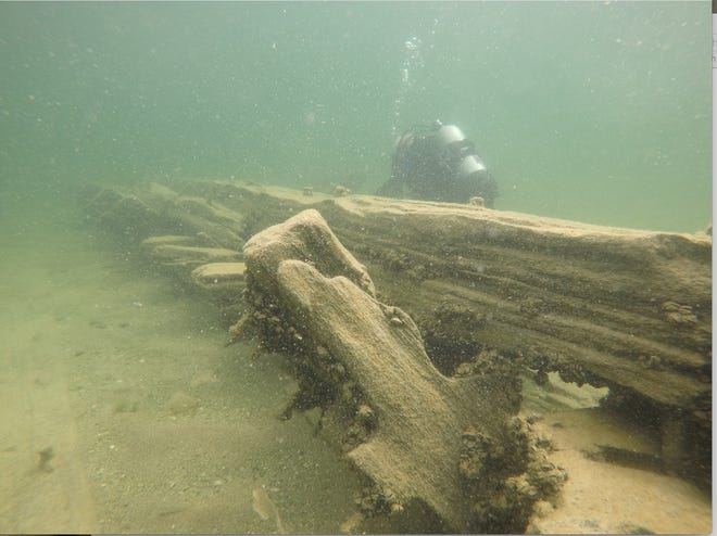 Diver Al Pertner, of Charlevoix, examines the keelson and frames of a shipwreck found in 2018 in Lake Michigan. Pertner analyzed the architectural evidence of the ship to determine its age.