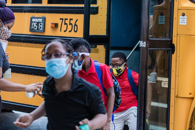 Teacher's aid Andresa Holzandorf greets students and sprays sanitizer into their hands as they get off the bus at Lincoln Elementary School in Riviera Beach on Sept. 21, 2020,  the first day of in person schooling after the outbreak of the COVID-19 pandemic.