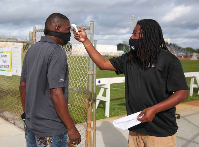 Eugene Johnson, 48, of Palm Beach Lakes, left, waits as Palm Beach Lakes Assistant Athletic Director James Powell takes his temperature as part of the Covid-19 screening protocol prior to the start of the game between Palm Beach Lakes and Palm Beach Gardens played at Jupiter Community High School in Jupiter, FL, on Saturday, October 31, 2020. Final score, Palm Beach Gardens, 16, Palm Beach Gardens, 8.