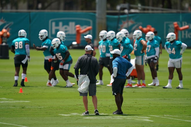 Brian Flores (right) watches minicamp practice this week.