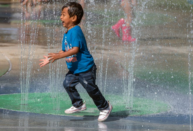 Two-year-old Ryden Phouminavoung of Stockton has fun cooling off from the heat in the interactive fountain near the Camanche picnic area of Micke Grove Park in Lodi.