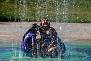 Six-year-old Viviana Guarduno, left, and 7-year-old Athena Bellrichar, both of Stockton, cool off from the heat in the interactive fountain near the Camanche picnic area of Micke Grove Park in Lodi.