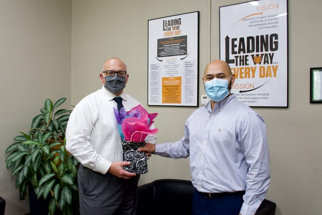 Gilbert Guzman, volunteer supervisor of Pulaski County for the Court Appointed Special Advocates of South Central Missouri, pictured right, presents Dr. Brian Henry, superintendent, with approximately 35 gift cards.