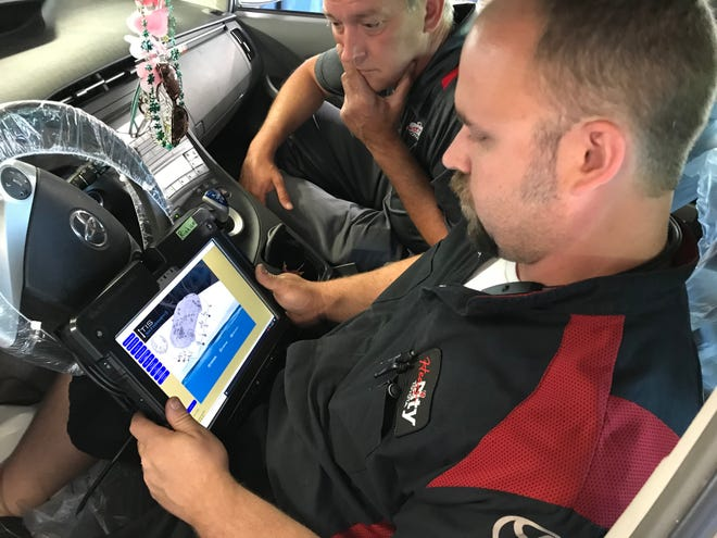 Kent Lochmandy watches Scott Kidder, a master diagnostic technician, as he works to solve a problem on a Toyota at Heart City Toyota in Elkhart