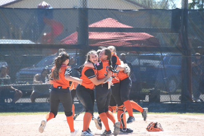 A group of Rudyard players celebrate at the pitcher's circle following a 4-1 quarterfinal win over Hillman Tuesday. Rudyard advances to the semifinals for the first time in school history.