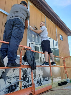 Artist Nick Worley, left, returned to Kewanee Monday to assist in installing his Mr. Baseball mural at Northeast Park. The mural project is an IDOC social justice initiative project that's been in the works for a year and a half.