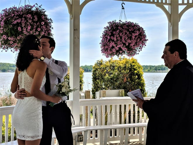 Michael Humphreys kisses his wife Agata Costa Ribeiro as they were married May 21 at Springfield Lake by Akron Municipal Court Judge Ron Cable.