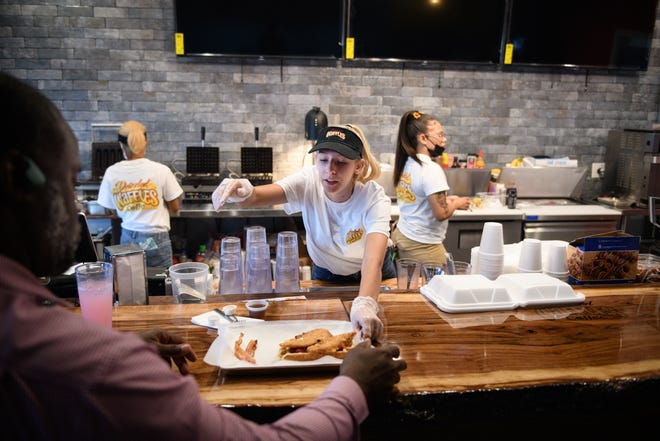 Courtney Hanson slides an order to a customer at Drizzled Waffles and Coffee restaurant at 3061 North Main St. in Hope Mills.