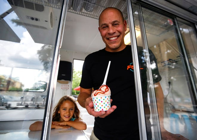 Joshua Broadhead holds a cup of guava ice cream in his family's ice cream truck, Feliz Flavors, at the Fourth Avenue Food Park on Tuesday, June 15, 2021 in Gainesville, Fla. His daughter, Kayla Broadhead, 7, smiles behind him. [Chasity Maynard/Special to The Sun]