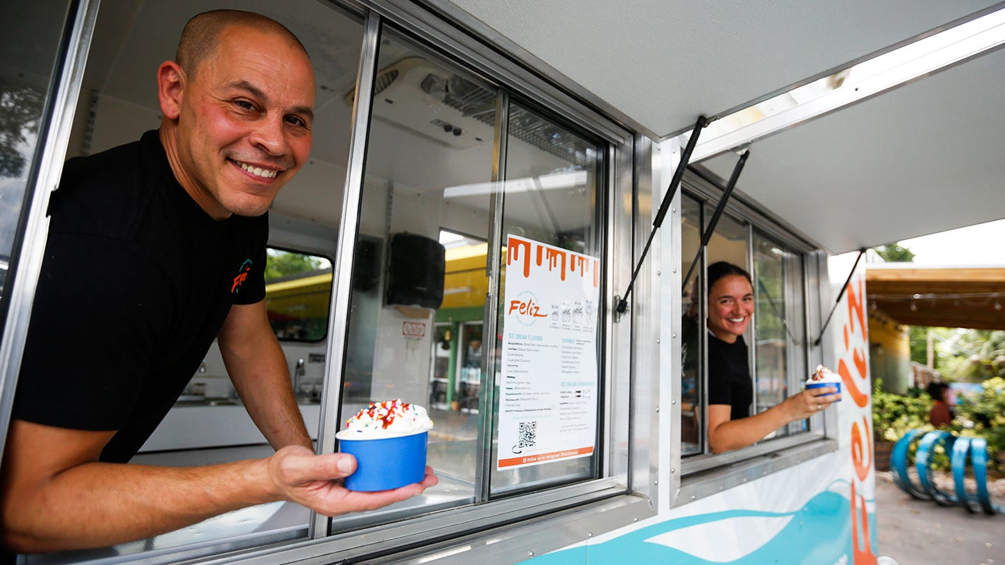 Joshua and Jasmine Broadhead lean out the windows of their ice cream truck, Feliz Flavors, at the Fourth Avenue Food Park on Tuesday, June 15, 2021 in Gainesville, Fla. [Chasity Maynard/Special to The Sun]