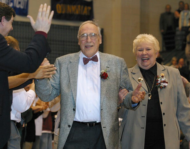 In this March 1, 2003, photo, Mount St. Mary's men's basketball coach Jim Phelan and his wife Dottie walk through a gauntlet of former players at Knott Arena in Emmitsburg, Md., after Phelan coached his last game.