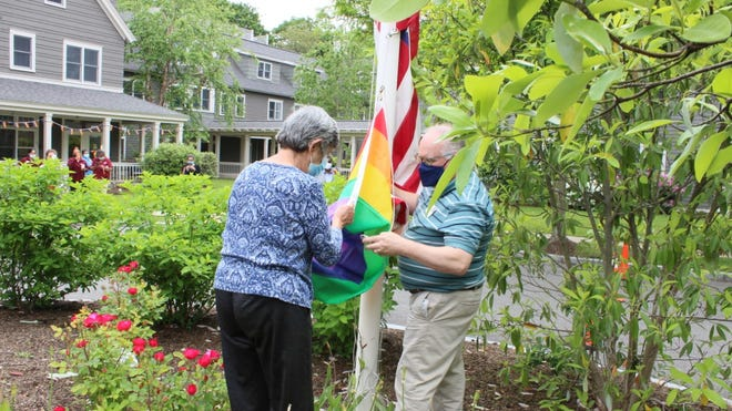 Goddard House resident Linda Shaver and assistant executive director Lance Chapman raise the LGBT Pride Flag on June 1.