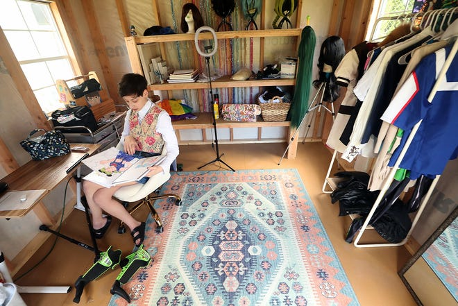 Nicole Buss flips through one of her many sketchpads inside her art studio on June 15. The studio, a shed in her backyard, was a donation through Make-A-Wish Alaska and Washington.