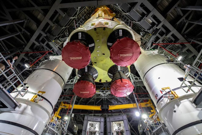 The core stage of NASA's Space Launch System rocket moves into place next to the boosters inside the VAB at Kennedy Space Center.