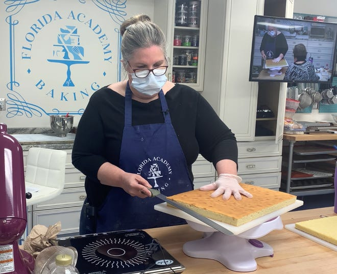 Chef Angela McEllen demonstrates how to level a sponge that will be used for petit fours during a Florida Academy of Baking class.