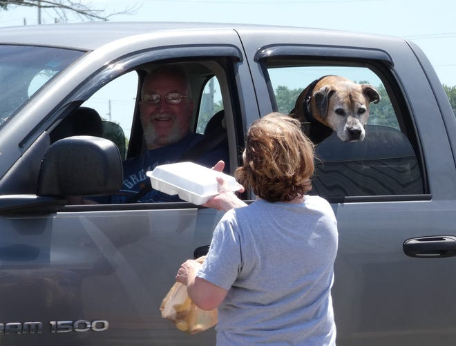 A dog sniffs optimistically as Kiwanis Club member Ida Foght delivers a meal during the annual chicken barbecue on Wednesday at the Crawford County Fairgrounds.