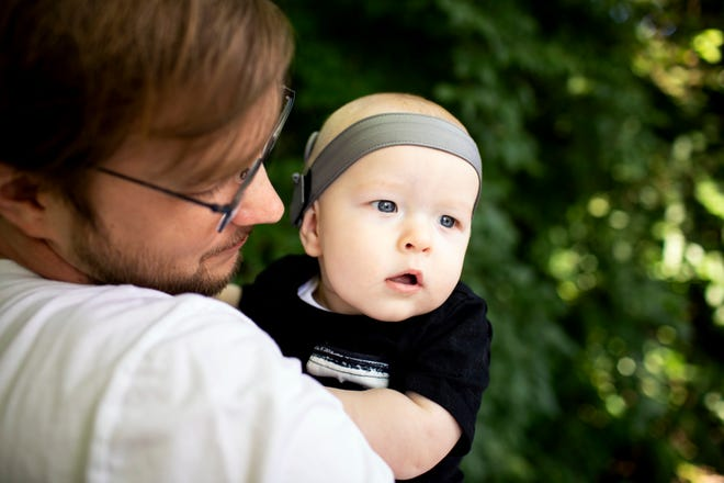 Enquirer reporter Keith BieryGolick holds his son in the backyard of his home on Tuesday, June 16, 2021 in Butler County.