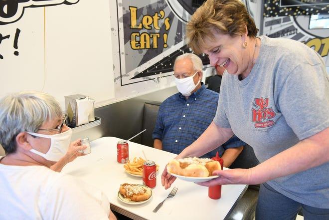 Ο συν-ιδιοκτήτης Carol Harlan, 63 ετών, εξυπηρετεί τον Coney προς τα αριστερά, τη Mary Jo και τον Gordy Ludwig του Warren στο Red Hots Coney Island στο Highland Park του Μίσιγκαν στις 15 Ιουνίου 2021. Ο Γκόρντι λέει ότι είναι στο Red Hots από το 1962.