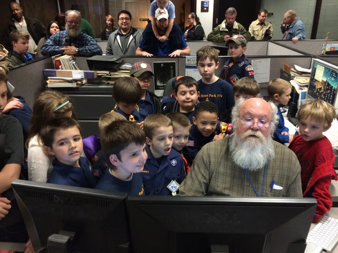 Kevin J. Swank, director of visuals at the Courier & Press, gives the Cub Scouts a lesson in picture editing during their tour of the newspaper Nov. 24, 2014.