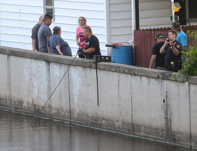Clayton Matulle (center) uses a grappling hook on a rope to try and re-hook what he believes was a human hand that he briefly pulled out of the water Tuesday, June 15, 2021 in the Fond du Lac River at the end of Lincoln Street near the Johnson Street bridge while Lt. Eric Foster (right) of the Fond du Lac Police Department talks on the phone.