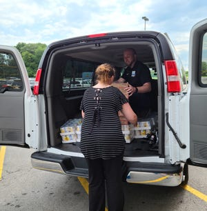 The Ottawa County Family Advocacy Center is distributing meals this summer. Kenny Edler of Kroger and Ashley Walterbusch from the center load 600 cans of vegetables and 1,100 Ramen noodle packages.