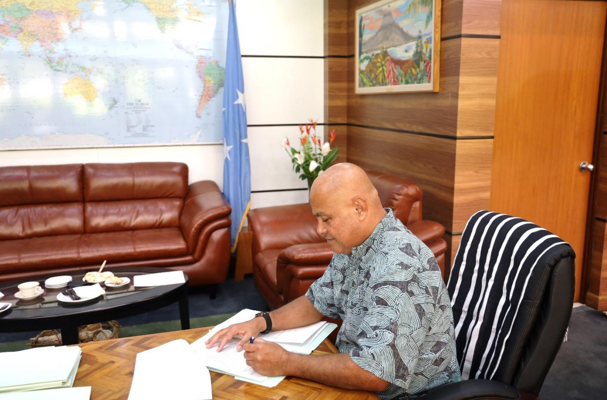 David W. Panuelo, president of the Federated States of Micronesia, signs his letter to U.S. President Joe Biden. The FSM government has asked the U.S. to help pave roads within the FSM.