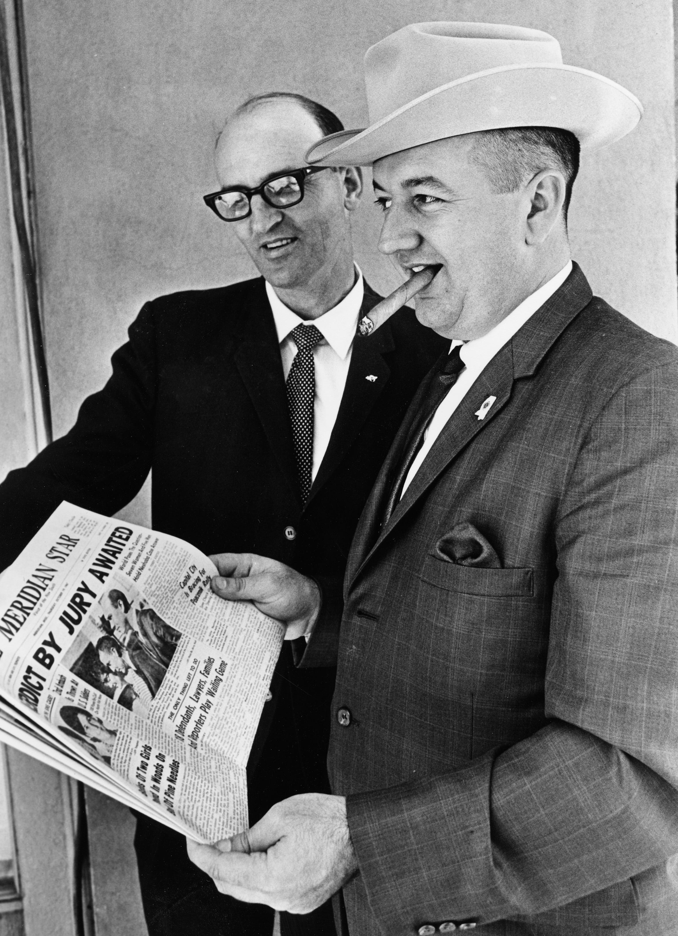 In this Oct. 19, 1967, file photo, Neshoba County Sheriff Deputy Cecil Price, right, holds a copy of the Meridian Star newspaper with Edgar Ray Killen, left, as they await their verdicts in the murder trial of three civil rights workers, James Chaney, Andrew Goodman and Michael Schwerner in Meridian, Miss.