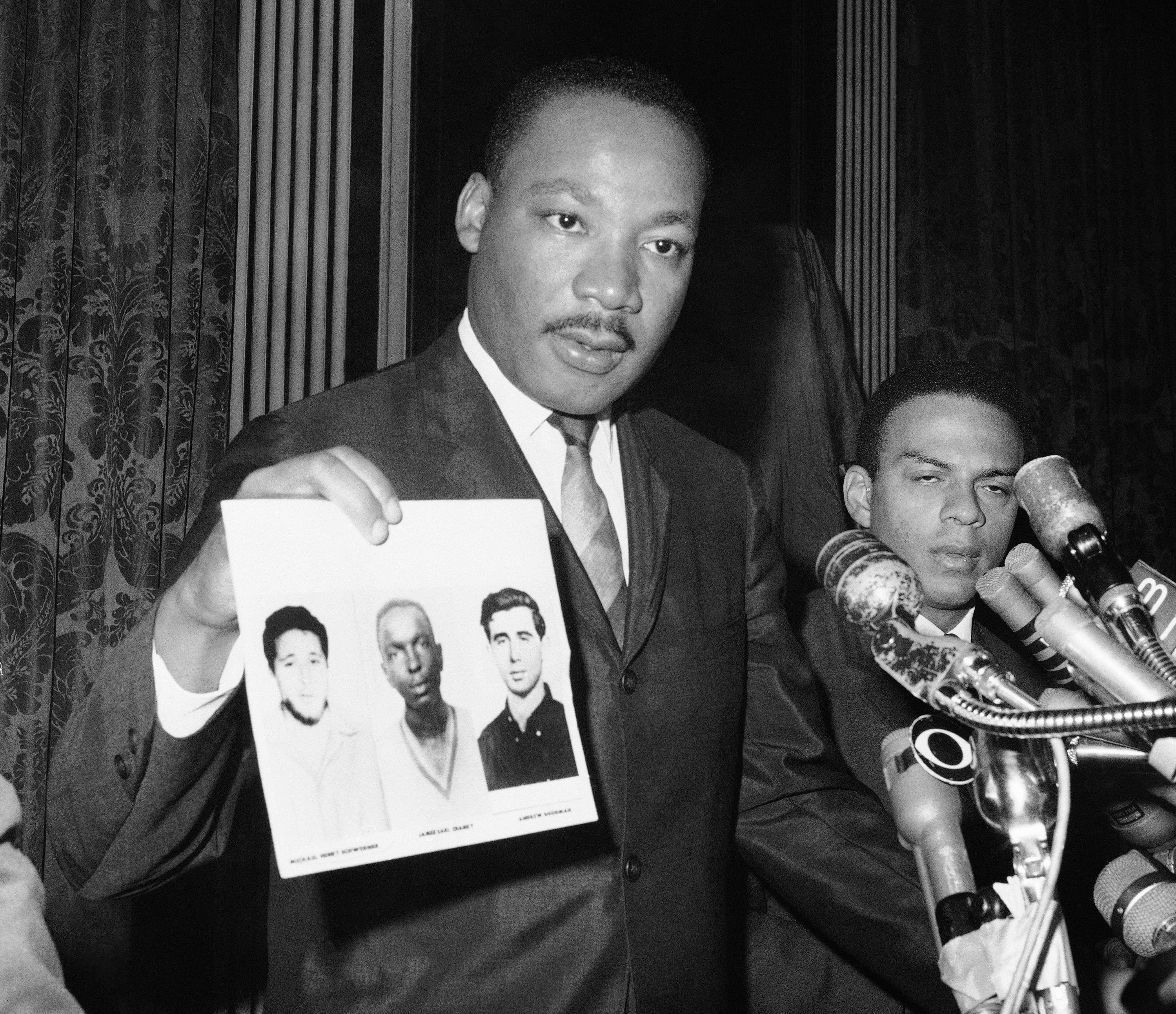 In this Dec. 4, 1964, file photo civil rights leader Martin Luther King Jr. displays pictures of three civil rights workers, who were slain in Mississippi the summer before, from left, Michael Schwerner, James Chaney and Andrew Goodman, at a news conference in New York, where he commended the FBI for its arrests in Mississippi in connection with the slayings.