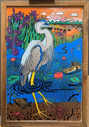"""Ben Koch, an art teacher at Broussard Middle School and an openly gay man, had his """"glow up blow up""""with the purchase of his piece at Scratch Farm Kitchen. It depicts a blue heron wading in a marsh teeming with life."""