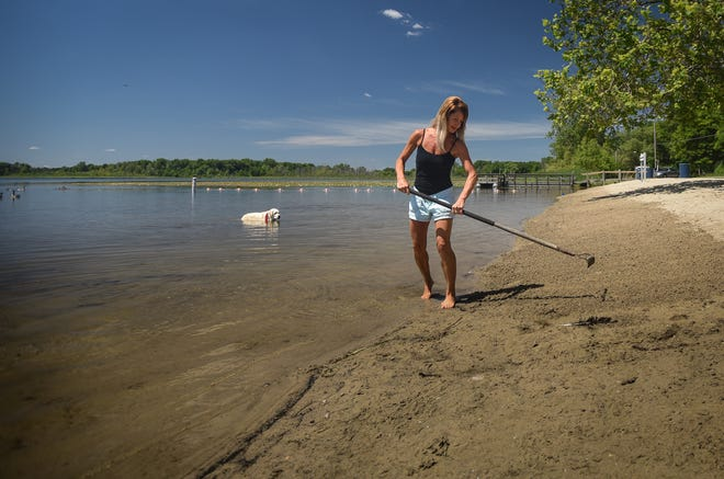 """""""I'm here every day in the summer Monday through Friday,"""" Jeanie Anello of Bath Township says Wednesday, June 16, 2021, as she rakes the sand near Park Lake clear of goose droppings and feathers."""