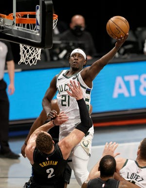 Jrue Holiday of the Milwaukee Bucks elevates for a layup over Blake Griffin of the Brooklyn Nets.