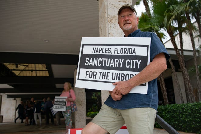Tim Carpenter, a Collier County resident, shows his support for outlawing abortion in the city of Naples, on  June 16 at Naples City Hall.