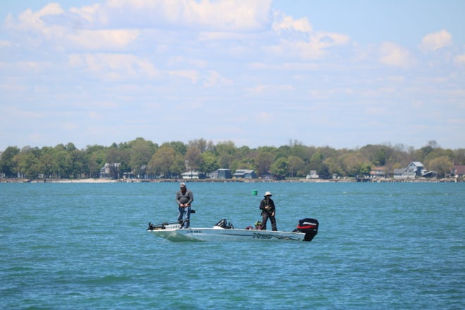 A pair of fishermen take advantage of the calmer weather to do some fishing out on Lake Erie, finding a spot near Put-in-Bay.