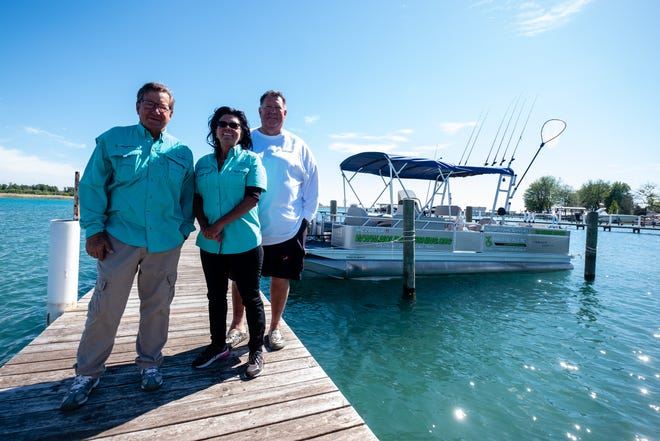 From left, vice president Dave Malkiewicz, first mate Belinda Smith and president Blair Hughes pose for a portrait Tuesday, June 15, 2021, next to No Limits Fishing Adventures Inc.'s boat in Clay Township.