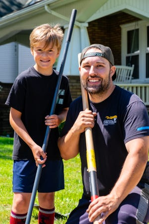 Gary Lokers and his son Eli, 8, pose for a portrait while working on a yard for Eli's Quick Cuts Lawncare, Monday, June 14, 2021, in Port Huron. Lokers and his son started the business in 2019.