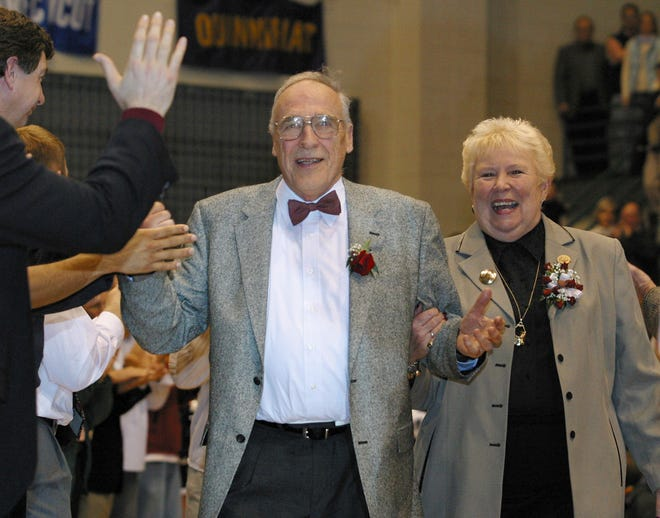 FILE - Mount St. Mary's men's NCAA college basketball coach Jim Phelan and his wife Dottie walk through a gauntlet of former players at Knott Arena in Emmitsburg, Md., after Phelan coached his last game as coach, in this Saturday, March 1, 2003, file photo. Phelan, the bow-tied basketball coach who won 830 games during nearly a half-century at Mount St. Mary's, has died. He was 92. The athletic department at Mount St. Mary's said Phelan died in his sleep at home Tuesday night, June 15, 2021. (AP Photo/Timothy Jacobsen, File)