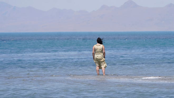 Amelia Gotbetter stands at the Great Salt Lake Tuesday, June 15, 2021, near Salt Lake City. Salt Lake City set another heat record Tuesday, June 15, 2021, and experienced its hottest day of the year as the state's record-breaking heat wave persists. Utah's capitol hit 104 degrees, breaking the previous heat record for that date of 103 degrees, according to information from the National Weather Service. On Monday, Salt Lake City hit 103 degrees to break a heat record for that date set nearly 50 years ago. (AP Photo/Rick Bowmer)