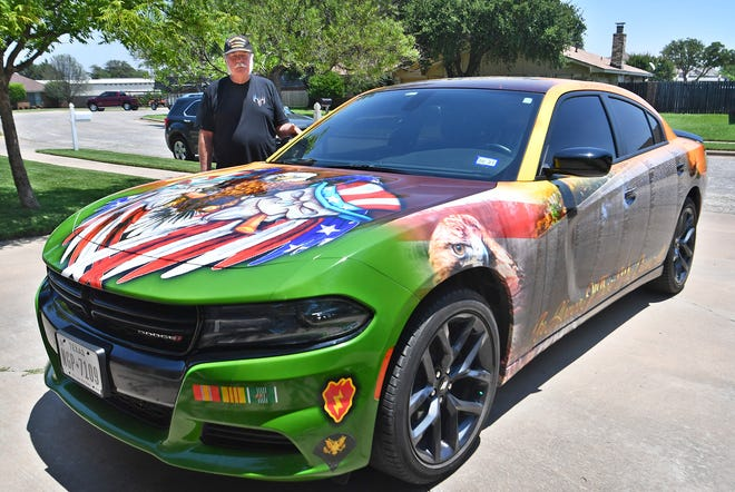 Alvin Brannon stands beside his 2019 Dodge Charger that he had wrapped with patriotic images and military insignias from his service in the Vietnam War.