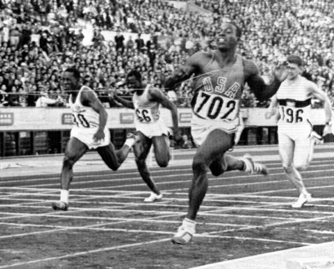 Bob Hayes hits the tape to win the 100-meter dash final at the Olympic Games in Tokyo, Oct. 15, 1964. Cuba's Enrique Figuerola, left, finished second. Second from left is Gaoussou Kone, of the Ivory Coast, and Heinz Schumann, of Germany, is at right.