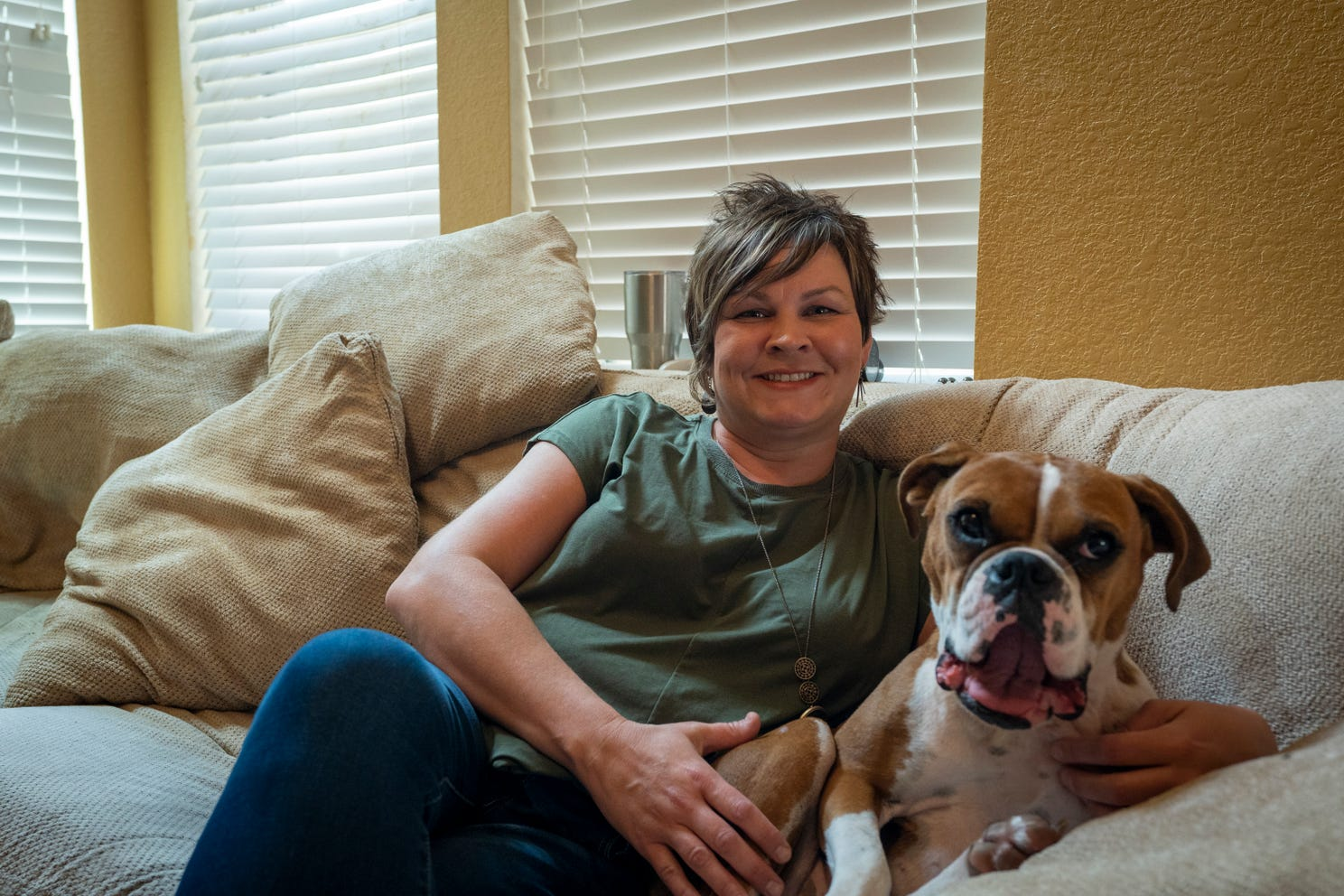 Kara Shepherd, a labor and delivery nurse at Houston Methodist Willowbrook Hospital, sits with a dog in the home of Jennifer Bridges. Shepherd says of the hospital's recent COVID-19 vaccine mandate for employees,