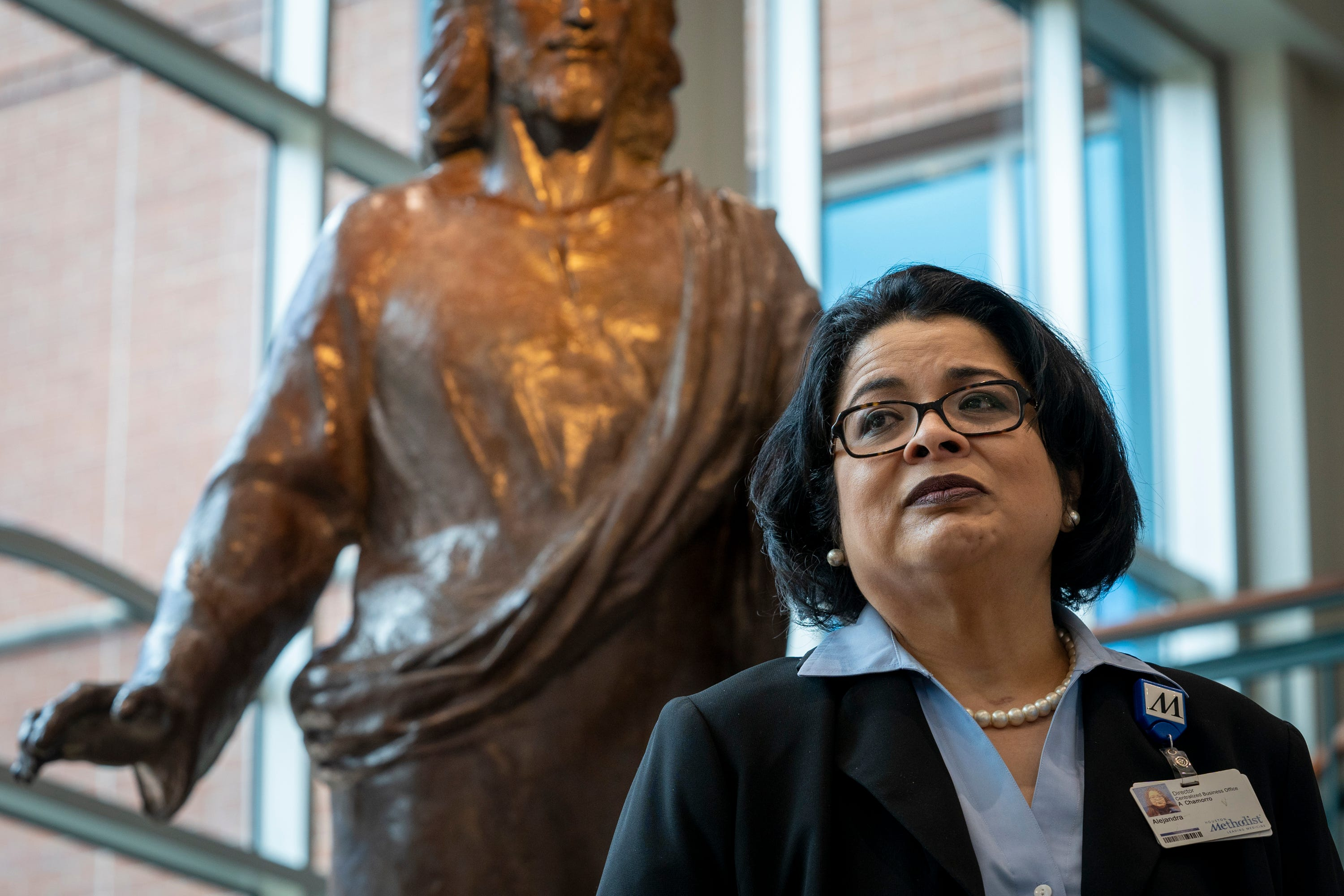 """Alejandra """"Alex"""" Chamorro, who oversees insurance billing for the hospital system, in front of a statue of """"Jesus-The Great Physician"""" in the lobby of the Houston Methodist Continuing Care Hospital facility."""