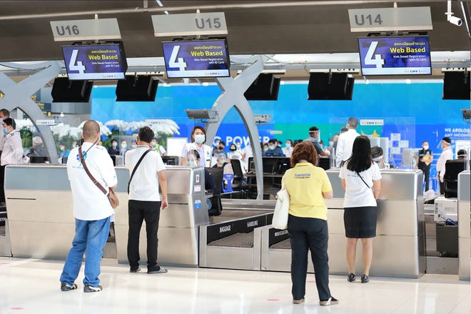 This handout photo from Airports of Thailand taken and released on April 26, 2021, shows airport workers queuing up at a check-in counter during the process for their COVID-19 vaccination at Suvarnabhumi Airport in Bangkok.
