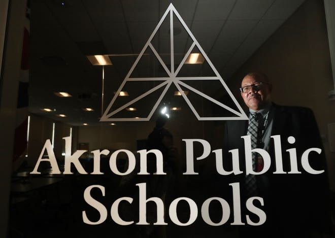David James, retiring superintendent of Akron Public School, is reflected in a window with the APS logo in the school boardroom.