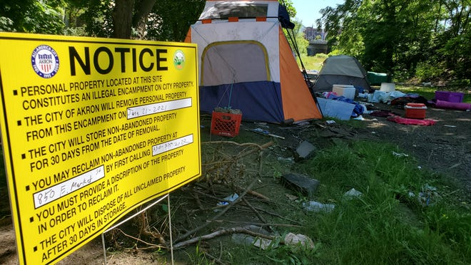 """Signs posted last week in Grace Park in downtown Akron state the city would clear encampments in the vicinity starting Monday. Tents and other belongings pictured in the background were left behind by people who recently accepted housing vouchersfrom Community Support Services, as the city begins a """"Housing First"""" policy, while clearing encampments."""