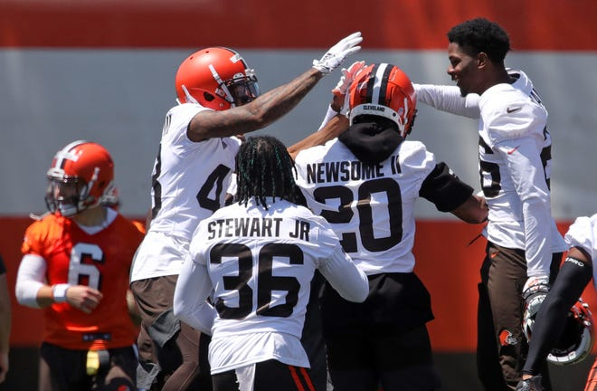 Cleveland Browns rookie cornerback Greg Newsome II, center, is congratulated by teammates John Johnson III, left, and Greedy Williams, right, after picking off a pass thrown by quarterback Baker Mayfield during an NFL football practice at the team's training facility, Thursday, June 17, 2021, in Berea, Ohio. [Jeff Lange / Akron Beacon Journal]