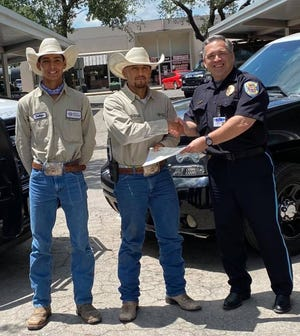 Wyatt Ranches associates Walter Mencias, Division Livestock Foreman, and Santiago Vela, Mansion Attendant from the Los Robles Division of Wyatt Ranches present a grant check in the amount of $137,500 to Eden Garcia, Chief of Police of the Alice Police Department.