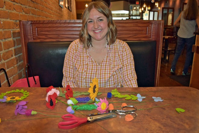 Chelsea Trowbridge of Huxley poses with some of her Wildflower Gift Shop creations during an interview at Cafe Diem. The felt wildflowers and other products are available from her Etsy shop.