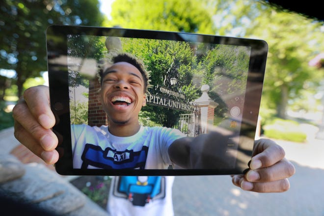 Jonathan Brown,  a 19-year-old junior from Cincinnati majoring inpolitical science and media production, holds up his new iPad, courtesy of a new initiative at Capital University. The Bexley university is giving every student, staff member and faculty member an iPad in an effort to level the playing field and bolster student success.