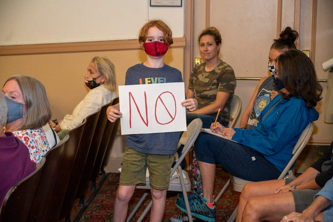 """A child holds up a sign saying """"NO"""" to the proposed height amendment at a town hall meeting in Mount Dora on Monday night. [Cindy Peterson/Correspondent]"""